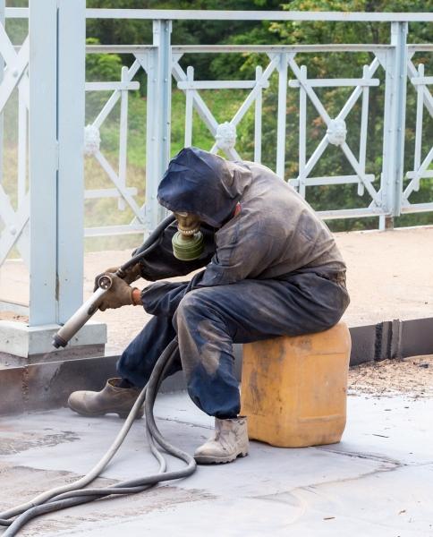 Εργάτης πραγματοποιεί αμμοβολή σε μεταλλική επιφάνεια